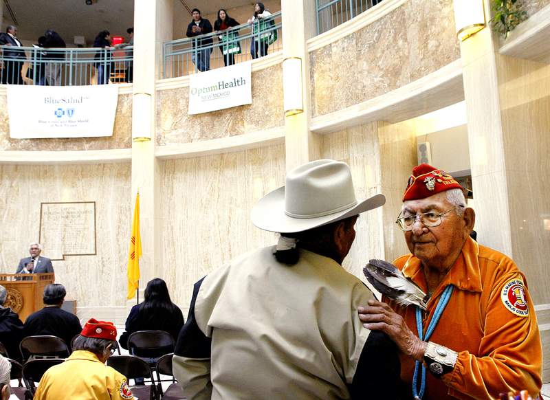 """FILE - In this Feb. 4, 2011, file photo, Leland Anthony, Arizona Rep. for Indian Health Incorp., left, speaks with Navajo code talker Joe Vandever Sr. during Native American Day at the roundhouse in Santa Fe, New Mexico. One of the few remaining Navajo Code Talkers who used their native language to confound the Japanese in World War II has died. Joe Vandever Sr. died of health complications Friday, Jan. 31, 2020, in Haystack, New Mexico, west of Grants, according to his family. He was 96. Tribal leaders called Vandever a """"great warrior"""" and a """"compassionate family man,"""" and asked Navajos to keep his spirit and his family in their prayers. (Jane Phillips/The New Mexican via AP)"""