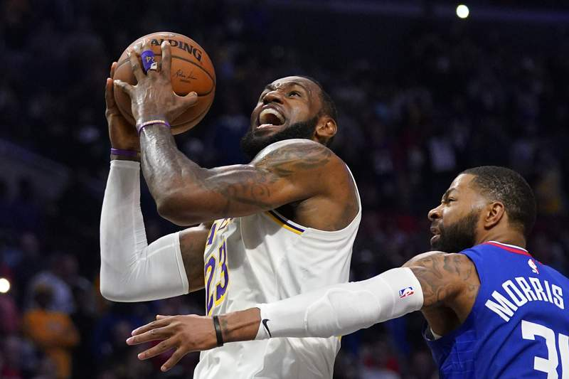 FILE - In this March 8, 2020, file photo, Los Angeles Lakers forward LeBron James, left, shoots as Los Angeles Clippers forward Marcus Morris Sr. defends during the second half of an NBA basketball game in Los Angeles. LeBron James says he probably won't feel any closure on the Los Angeles Lakers' remarkable season unless the NBA is able to finish its season. (AP Photo/Mark J. Terrill, File)