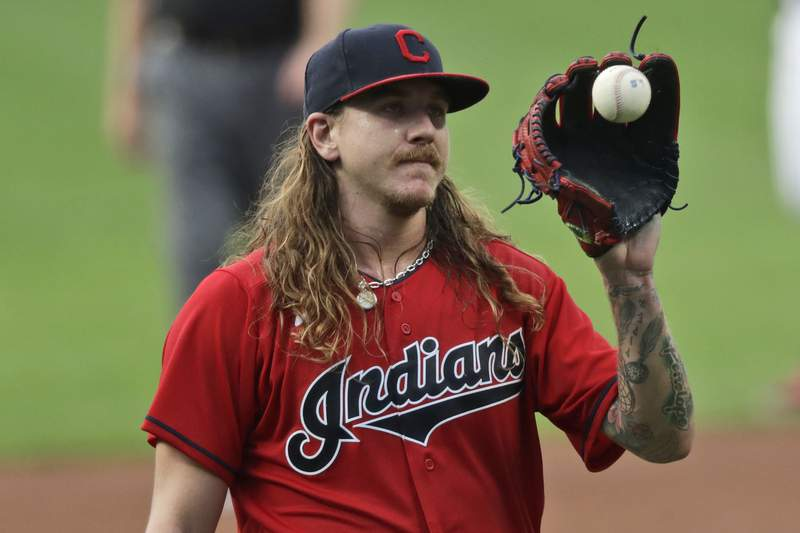 Cleveland Indians starting pitcher Mike Clevinger gets another ball after giving up a home run in the first inning in a baseball game, Wednesday, Aug. 26, 2020, in Cleveland. (AP Photo/Tony Dejak)