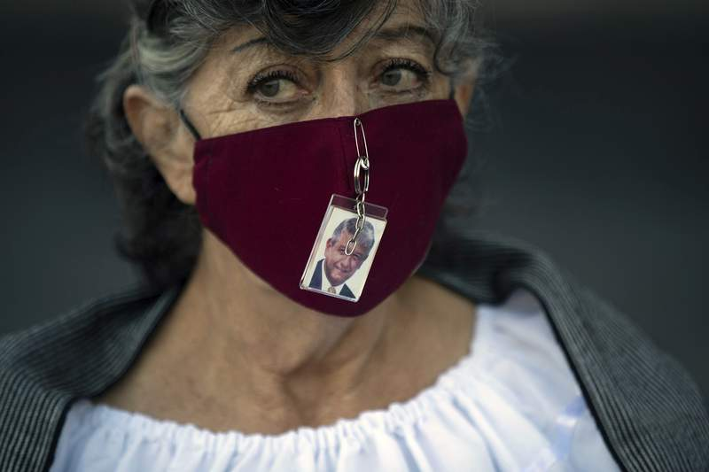 A supporter of Mexican President Andres Manuel Lopez Obrador wears a mask with a photo of him pinned to it outside the presidential palace as the president delivers his second state-of-the-union address inside, in Mexico City, Tuesday, Sept. 1, 2020. Obrador emphasized what he considers his major achievements: the fight against corruption and his governments austerity. (AP Photo/Fernando Llano)