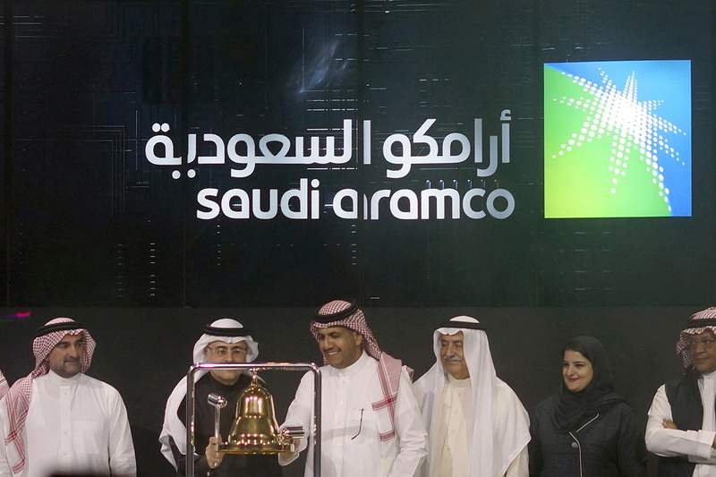 FILE - In this Dec. 11, 2019, file photo, Saudi Arabia's state-owned oil company Armco and stock market officials celebrate during the official ceremony marking the debut of Aramco's initial public offering (IPO) on the Riyadh's stock market, in Riyadh, Saudi Arabia. Saudi Arabia's oil giant Aramco announced Monday, Nov. 16, 2020, it will issue international bonds as it seeks a cash infusion to help pay for billions of dollars in dividends the company promised shareholders before the global coronavirus pandemic sent oil prices plummeting. (AP Photo/Amr Nabil, File)