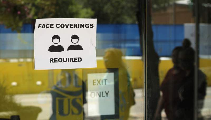 A sign requiring people to wear face coverings.