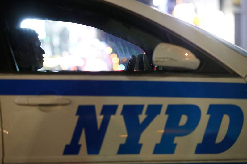 """FILE - In this Dec. 31, 2015, file photo, a New York City police officer sits in a cruiser at a checkpoint surrounding Times Square during New Year's Eve celebrations in New York. The vast majority of complaints about New York City police officers' mistreatment of youths stemmed from encounters with black and Hispanic children, according to a new study by the citys police watchdog agency. Nearly two-thirds of youth complaints to the Civilian Complaint Review Board involved children of color, the report says, including some stopped for seemingly innocuous activities such as playing, high-fiving, running, carrying backpacks, and jaywalking."""" (AP Photo/Julio Cortez, File)"""