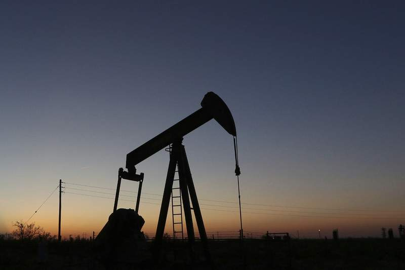 FILE - In this June 11, 2019, photo a pump jack operates in an oil field in the Permian Basin in Texas. The world may be heading into an oversupply of oil, and that possibility is hanging over members of the OPEC cartel, which will meet later this week to decide whether to further cut production to boost prices. (Jacob Ford/Odessa American via AP, File)