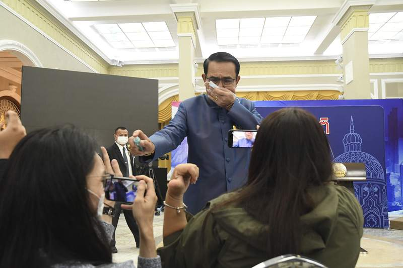 Thailand's Prime Minister Prayuth Chan-ocha sprays alcohol mist on a front row of reporters sitting inside the press conference room at Government house in Bangkok, Thailand, Tuesday, March 9 , 2021. Riled by a final question about a possible Cabinet reshuffle, the prime minister told reporters to mind their own business, then grabbed a container of alcohol mist and doused the front row before sauntering off. (AP Photo)