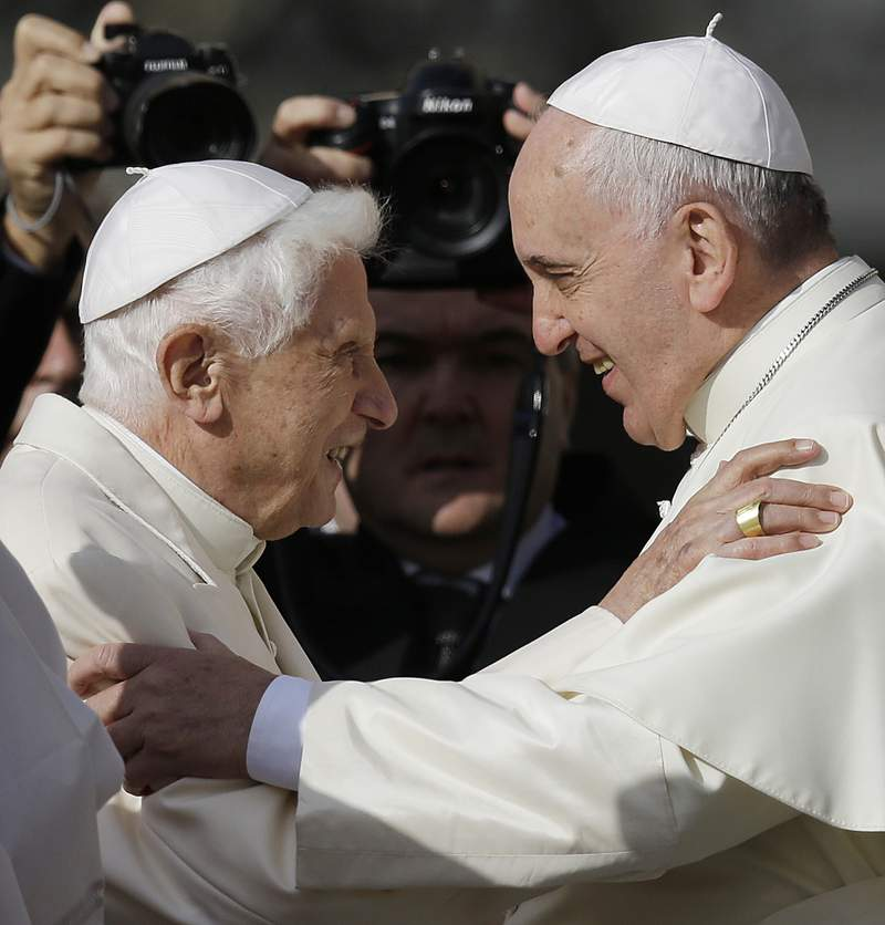 FILE - In this Sept. 28, 2014 file photo, Pope Francis, right, hugs Pope Benedict XVI prior to the start of a meeting with elderly faithful in St. Peter's Square at the Vatican. Retired Pope Benedict XVI has broken his silence to reaffirm the value of priestly celibacy, co-authoring a bombshell book at the precise moment that Pope Francis is weighing whether to allow married men to be ordained to address the Catholic priest shortage. (AP Photo/Gregorio Borgia, File)