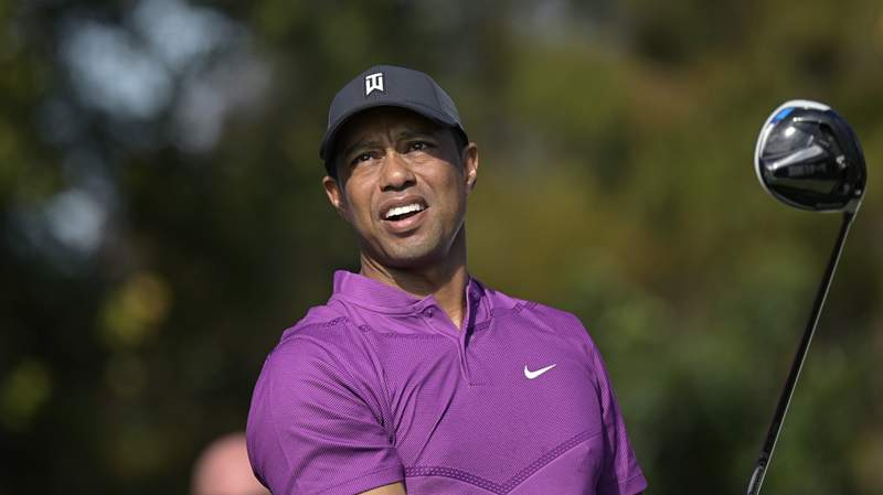 File-This Dec. 19, 2020, file photo shows Tiger Woods watching his tee shot on the first hole during the first round of the PNC Championship golf tournament, in Orlando, Fla. Woods announced Tuesday, Jan. 19, 2021, he had a fifth back surgery and will miss tournaments in San Diego and Los Angeles. (AP Photo/Phelan M. Ebenhack, File)