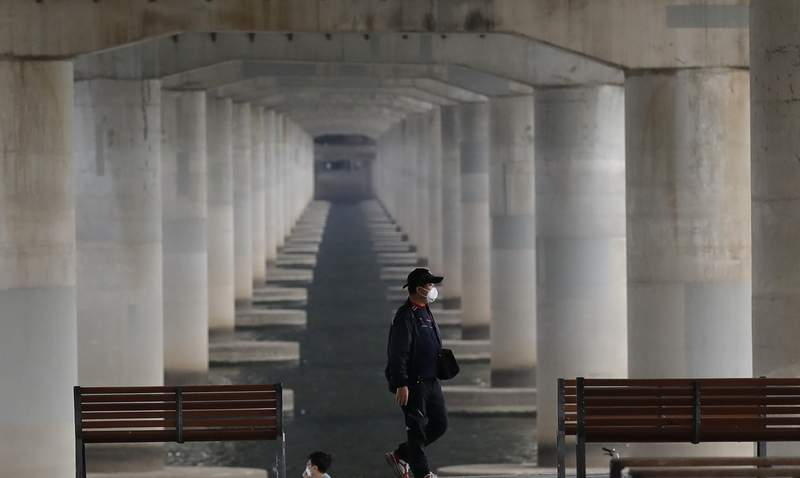 A man wearing a face mask to help protect against the spread of the new coronavirus walks along the Han River at a park in Seoul, South Korea, Sunday, April 19, 2020. South Korea's prime minister says the country will maintain much of its social distancing guidelines until May 5 but will relax some limits. (AP Photo/Lee Jin-man)
