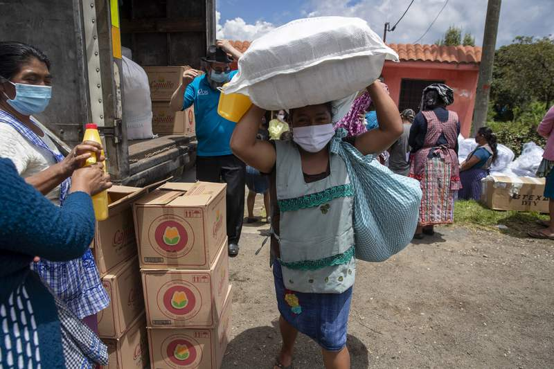 A woman wearing a protective face makes her way home with bagfuls of aid, in San Jose Calderas, Guatemala, Wednesday, Sept. 9, 2020, amid the new coronavirus pandemic. The governments migrant support agency Conamigua, delivered bags of food and household items to the community of people who have been deported from the United States affected by COVID-19. (AP Photo/Moises Castillo)