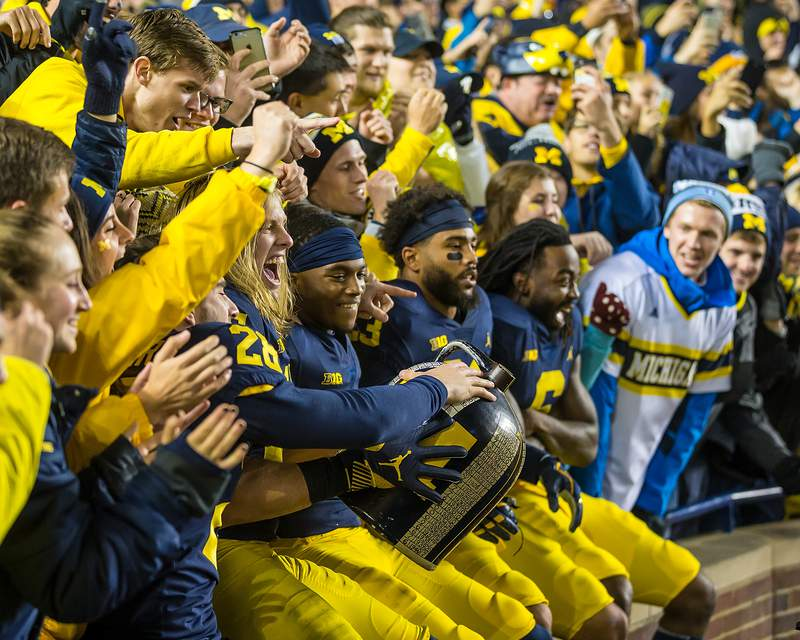 Michigan football players celebrate with the Little Brown Jug after Michigan's last meeting with Minnesota, in 2017.