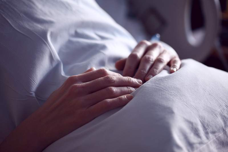 A patient holding a pillow in a hospital bed.