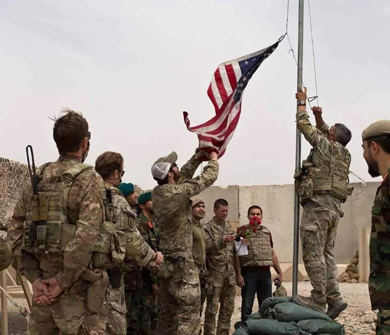 A U.S. flag is lowered as American and Afghan soldiers attend a handover ceremony from the U.S. Army to the Afghan National Army, at Camp Anthonic, in Helmand province, southern Afghanistan, Sunday, May 2, 2021. (Afghan Ministry of Defense Press Office via AP)