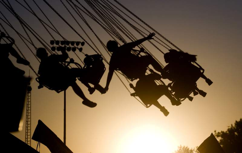 FILE - In this July 23, 2009 file photo, children are silhouetted by the setting sun as they ride a swing ride during the Canyon County Fair in Caldwell, Idaho. New results published Monday, Dec. 9, 2019,  in JAMA Pediatrics from the largest long-term study of brain development and childrens health raise provocative questions about obesity and brain function.   (Greg Kreller/The Idaho Press-Tribune via AP, File)