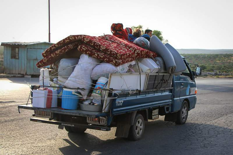 This photo provided by the Syrian Civil Defense White Helmets, which has been authenticated based on its contents and other AP reporting, shows Syrians in a pickup with their belongings, as they flee fighting in the villages of Jabal al-Zawiya, Syria, Tuesday, June 9, 2020. Syrian activists and a war monitoring group say that dozens of suspected Russian airstrikes have pounded villages on the edge of the last rebel enclave in northwestern Syria, sending thousands of civilians fleeing. The escalation began on Monday and is the most serious breach of a Russia-Turkey brokered cease-fire in place since March. (Syrian Civil Defense White Helmets via AP)