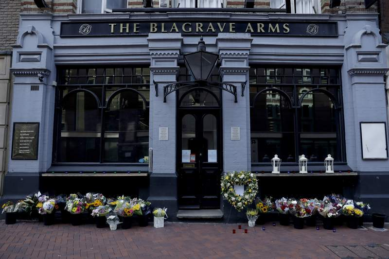 FILE - In this Tuesday, June 23, 2020 file photo, flowers are placed outside the Blagrave Arms pub near the scene of a fatal multiple stabbing attack in Forbury Gardens park, in Reading, England. A 26-year-old Libyan man pleaded guilty to murder on Wednesday, Nov. 11 for stabbing three men to death as they sat in an English city park. Khairi Saadallah admitted three counts of murder and three of attempted murder for the June 20 attack in Reading, 40 miles (64 kilometers) west of London. Friends James Furlong, David Wails and Joseph Ritchie-Bennett were enjoying a warm Saturday evening in the towns Forbury Gardens park when they were stabbed. (AP Photo/Matt Dunham, file)