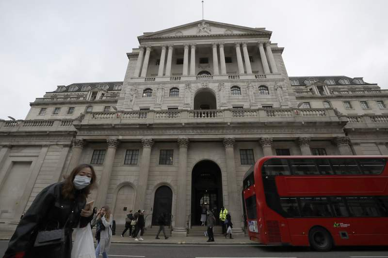 FILE - In this file photo dated Wednesday, March 11, 2020, pedestrians wearing face masks walk past the Bank of England in London.  The Bank of England kept its main interest rate unchanged at the record low of 0.1% on Thursday Sept. 17, 2020, as it waits to see how the economy recovers from recession and what Britains future trade relationship with the European Union will be. (AP Photo/Matt Dunham, FILE)