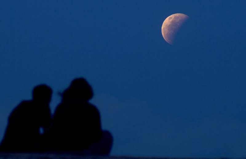 A couple watch the lunar eclipse at Sanur beach in Bali, Indonesia on Wednesday, May 26, 2021. The total lunar eclipse, also known as a super blood moon, is the first in two years with the reddish-orange color the result of all the sunrises and sunsets in Earth's atmosphere projected onto the surface of the eclipsed moon. (AP Photo/Firdia Lisnawati)