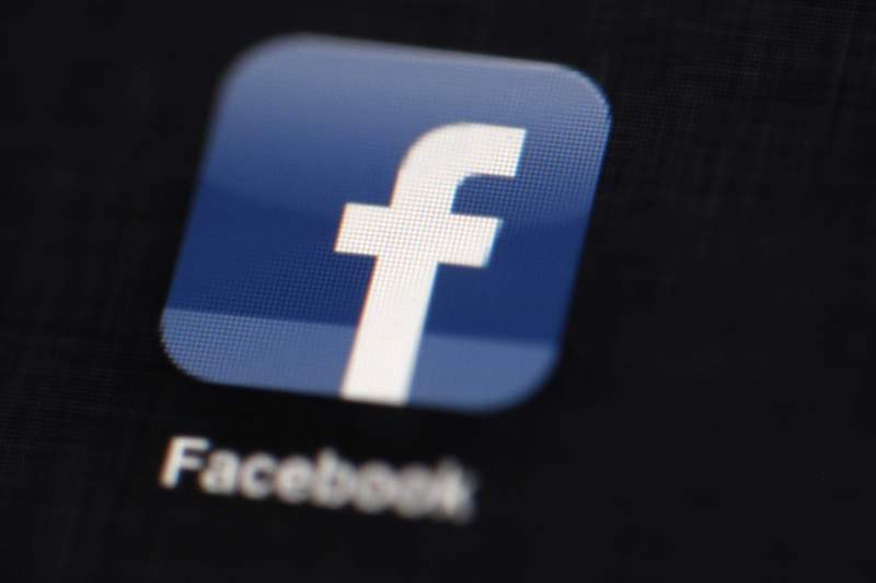 FILE - This May 16, 2012 file photo shows the Facebook logo displayed on an iPad in Philadelphia.  Facebook says it is lifting its ban on political and social-issue ads put in place after the 2020 U.S. presidential election. Political candidates, groups and others will be able to place such ads starting Thursday, March 3, 2021.  (AP Photo/Matt Rourke, File)