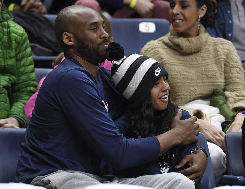 FILE - In this March 2, 2019, file photo Kobe Bryant and his daughter Gianna watch the first half of an NCAA college basketball game between Connecticut and Houston in Storrs, Conn. A public memorial service for Bryant, Gianna and seven others killed in a helicopter crash is planned for Monday, Feb. 24, 2020, at Staples Center in Los Angeles, a person with knowledge of the details told The Associated Press on Thursday, Feb. 6, 2020. (AP Photo/Jessica Hill, File)