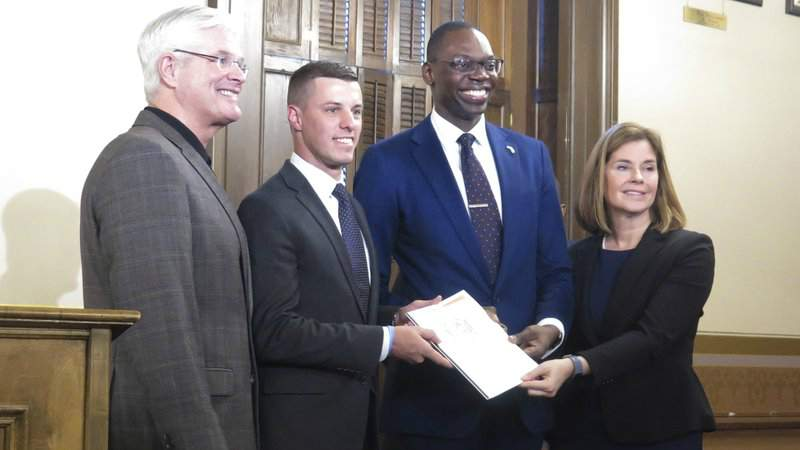 Michigan Supreme Court Chief Justice Bridget McCormack and Lt. Gov. Garlin Gilchrist, second from right, present a report on jail and pretrial incarceration to House Speaker Lee Chatfield, second from left, and Senate Majority Leader Mike Shirkey on Tuesday, Jan. 14, 2020 at the state Capitol in Lansing, Mich. A task force is recommending an overhaul to bail, arraignment timelines, sentencing and other policies after jail populations have tripled in under 40 years.