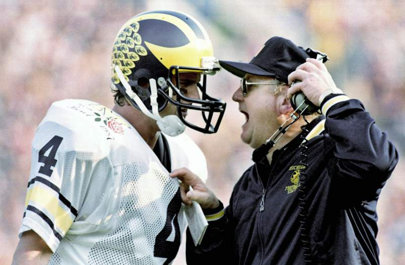FILE - In this Jan. 2, 1987, file photo, Michigan head coach Bo Schembechler yells at quarterback Jim Harbaugh during the Rose Bowl NCAA college football game in Pasadena, Calif. A report released Tuesday, May 11, 2021, about the stunning lack of action at the University of Michigan while a rogue doctor, Robert Anderson, was sexually assaulting hundreds of young men has pointed an unflattering light at one of the school's giants, the late football coach Bo Schembechler, whose bronze statue stands on campus. (AP Photo/Reed Saxon, File)