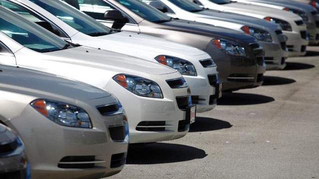 A line of used cars at a dealership.