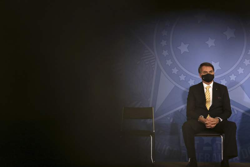 FILE - In this May 15, 2020, file photo, Brazil's President Jair Bolsonaro wears a mask amid the COVID-19 pandemic during an event at Planalto presidential palace in Brasilia, Brazil. Bolsonaro said Tuesday, July 7, he tested positive for COVID-19 after months of downplaying the viruss severity while deaths mounted rapidly inside the country. (AP Photo/Eraldo Peres, File)