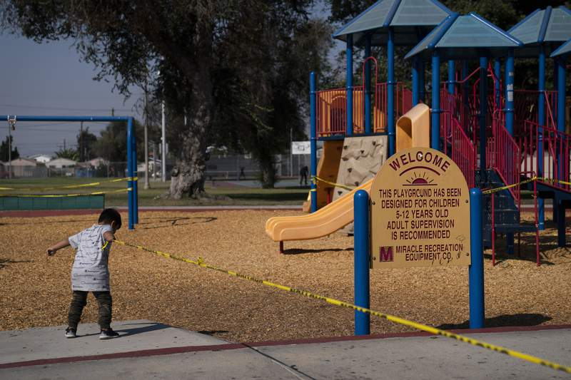 """Fernando Olvera, 5, pulls a string of yellow caution tape at a playground closed due to the coronavirus pandemic Thursday, Oct. 1, 2020, in South Central Los Angeles. California's plan to safely reopen its economy will begin to require counties to bring down coronavirus infection rates in disadvantaged communities that have been harder hit by the pandemic. The complex new rules set in place an """"equity metric"""" that will force larger counties to control the spread of the virus in areas where Black, Latino and Pacific Islander groups have suffered a disproportionate share of the cases due to a variety of socioeconomic factors. (AP Photo/Jae C. Hong)"""