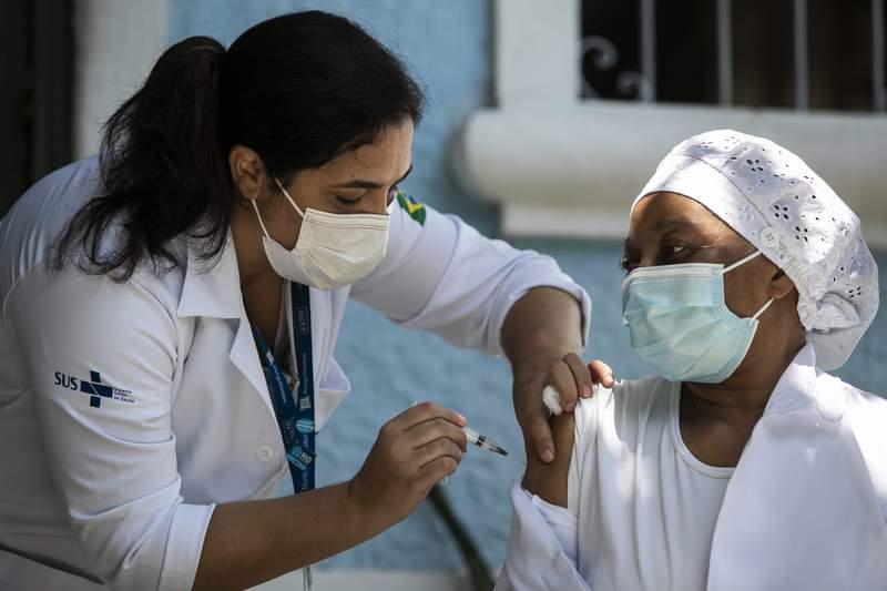 Nurse Angela Cassiano, 66, gets a shot of China's Sinovac CoronaVac vaccine at the retirement home where she works in Rio de Janeiro, Brazil, Wednesday, Jan. 20, 2021. (AP Photo/Bruna Prado)