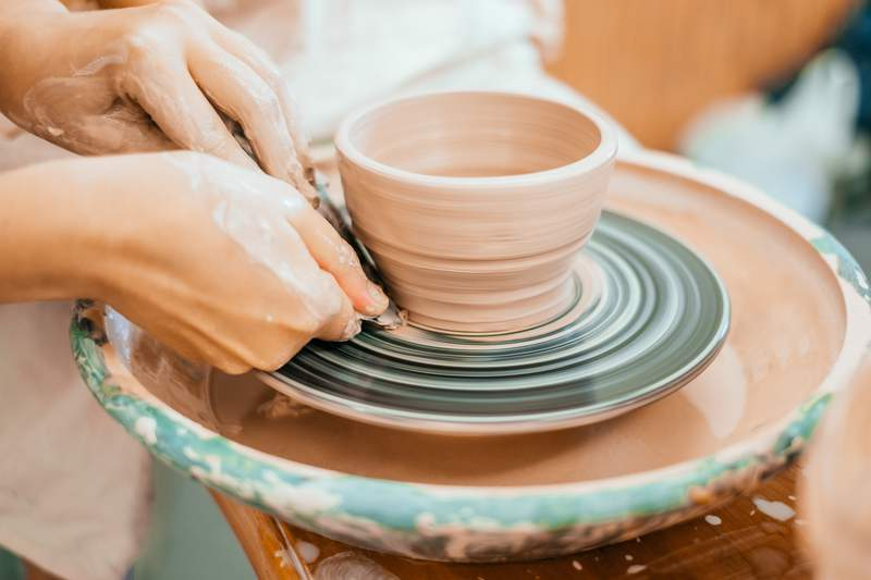 A woman works on a potter's wheel.