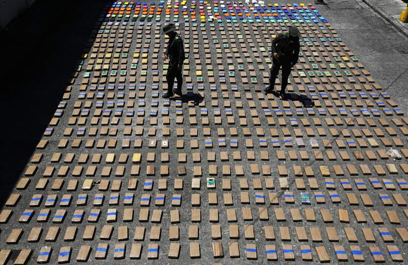 FILE - In this Thursday, Aug. 10, 2017 file photo, police officers walk among packages of seized cocaine at the Pacific port of Buenaventura, Colombia, after about one ton of cocaine was seized in a container during an operation by counternarcotics police at the port. In 2018, Capt. Juan Pablo Mosquera, a Colombian national police officer who was part of an elite unit that worked closely with U.S. anti-narcotics agents, was extradited to Miami to stand trial on charges he betrayed the U.S. Drug Enforcement Administration to the same traffickers they were jointly fighting. (AP Photo/Fernando Vergara)