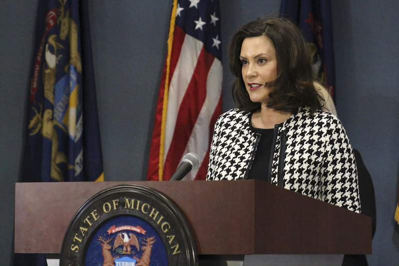 """FILE - In this April 20, 2020, file photo, provided by the Michigan Office of the Governor, Michigan Gov. Gretchen Whitmer addresses the state in Lansing, Mich. Whitmer said Tuesday that President Donald Trump's plan to suspend immigration is distracting from efforts to combat the coronavirus pandemic and part of """"inconsistent messages"""" that spread fear and put the public in """"greater danger."""" (Michigan Office of the Governor via AP, Pool, File)"""