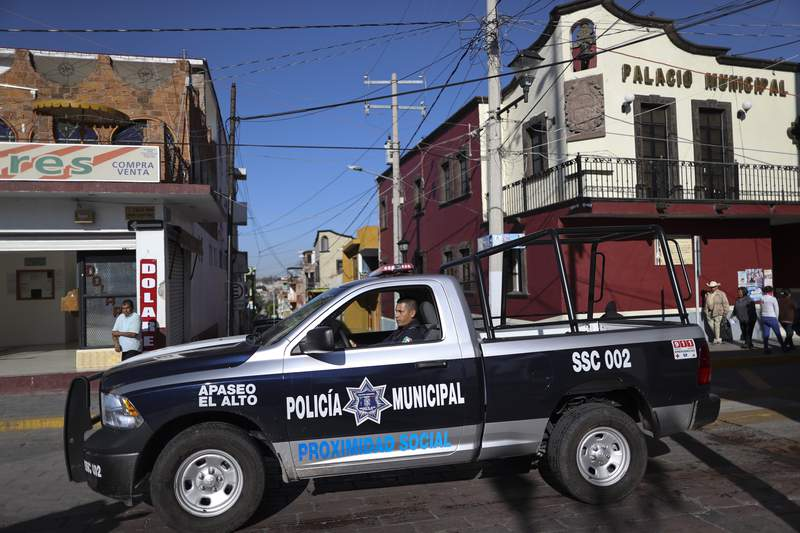 FILE - In this Feb. 10, 2020 file photo, a policeman drives past town hall in Apaseo El Alto, Guanajuato state, Mexico. The notoriously violent Jalisco cartel has responded to Mexico's hugs, not bullets policy with a policy of their own: the cartel kidnapped in mid-May 2021, several members of an elite police force in the state of Guanajuato, tortured them to obtain names and addresses of fellow officers, and are now hunting down and killing police at their homes, on their days off, in front of their families. (AP Photo/Rebecca Blackwell, File)