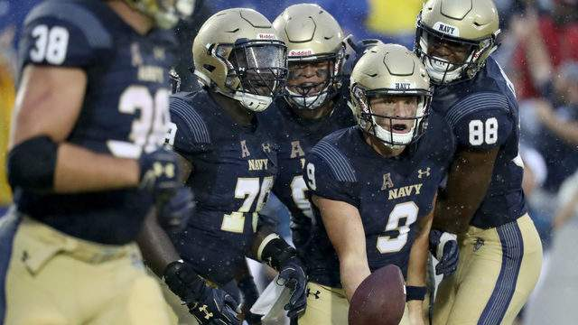 Zach Abey #9 of the Navy Midshipmen celebrates with teammates after rushing for the game winning touchdown against the Memphis Tigers at Navy-Marine Corps Memorial Stadium on September 8, 2018 in Annapolis, Maryland. (Photo by Rob Carr/Getty Images)