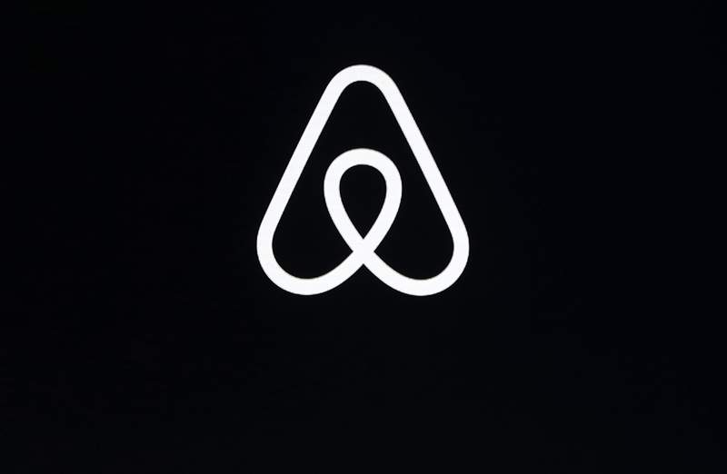 FILE - This Feb. 22, 2018, file photo shows an Airbnb logo during an event in San Francisco. Airbnb was losing money even before the pandemic struck and cut its revenue by almost a third, the home-sharing company revealed in documents filed Monday, Nov. 16, 2020, ahead of a planned initial public offering of its stock. (AP Photo/Eric Risberg, File)