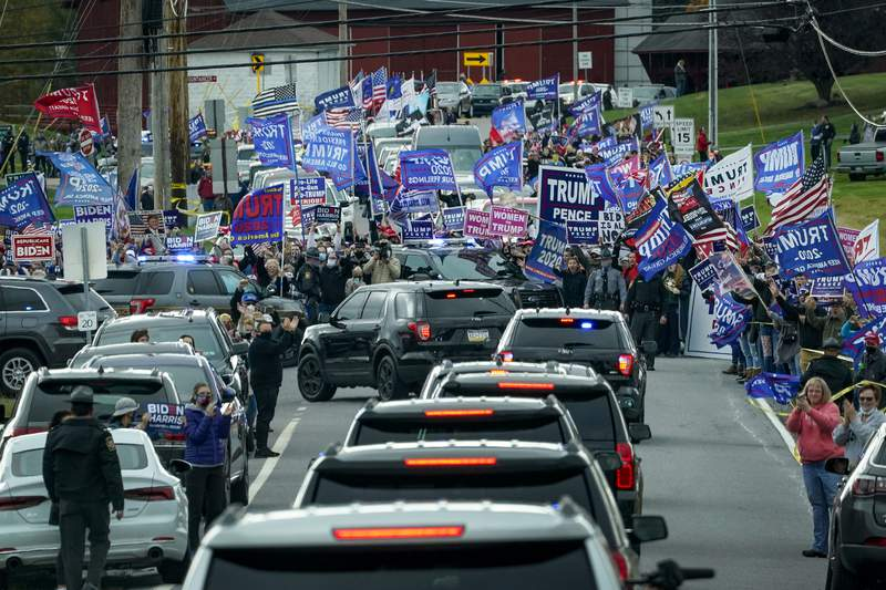 Supporters of President Donald Trump line the road as the motorcade for Democratic presidential nominee Joe Biden makes its way to a drive-in campaign rally at Dallas High School on Oct. 24, 2020 in Dallas, Pennsylvania.