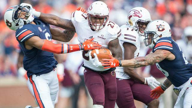 Running back Derrick Gore #27 of the Louisiana Monroe Warhawks stiff arms defensive back Carlton Davis #6 of the Auburn Tigers while looking to dodge defensive back Tray Matthews #28 of the Auburn Tigers at Jordan-Hare Stadium on November 18, 2017 in Auburn, Alabama. (Photo by Michael Chang/Getty Images)