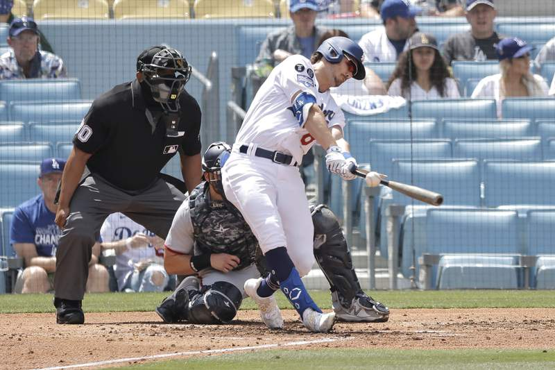 Zach McKinstry #8 of the Los Angeles Dodgers breaks his bat while hitting a foul ball against the Washington Nationals during the second inning at Dodger Stadium on April 11, 2021 in Los Angeles, California.