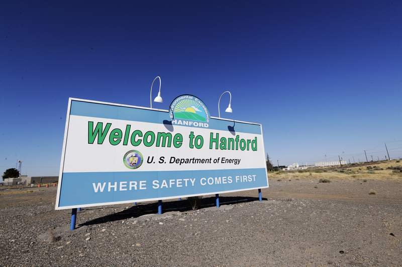FILE - In this Aug. 13, 2019, file photo, a sign at the Hanford Nuclear Reservation is posted near Richland, Wash. Two companies that do work at the former nuclear weapons production plant will pay fines of nearly $58 million for improperly billing the federal government for thousands of hours of work that were not performed. (AP Photo/Elaine Thompson, File)