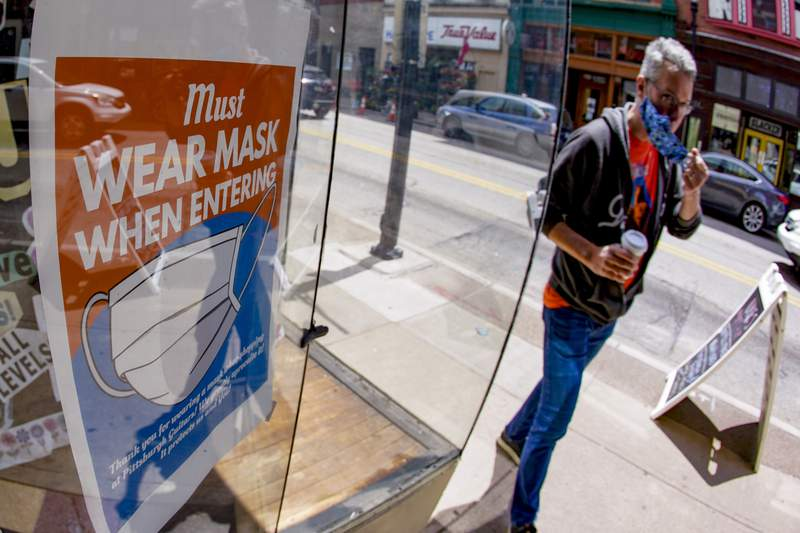 John Bechtold puts his face covering on as he passes his storefront sign that lists COVID-19 protective covering required to enter in his retail shop, Friday, May 14, 2021, in Pittsburgh's South Side neighborhood. (AP Photo/Keith Srakocic)