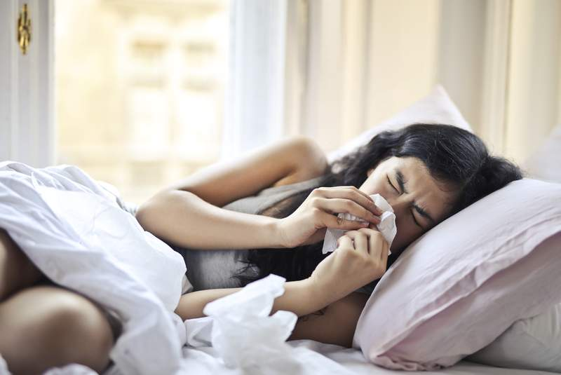 A sick woman sneezes while in bed.