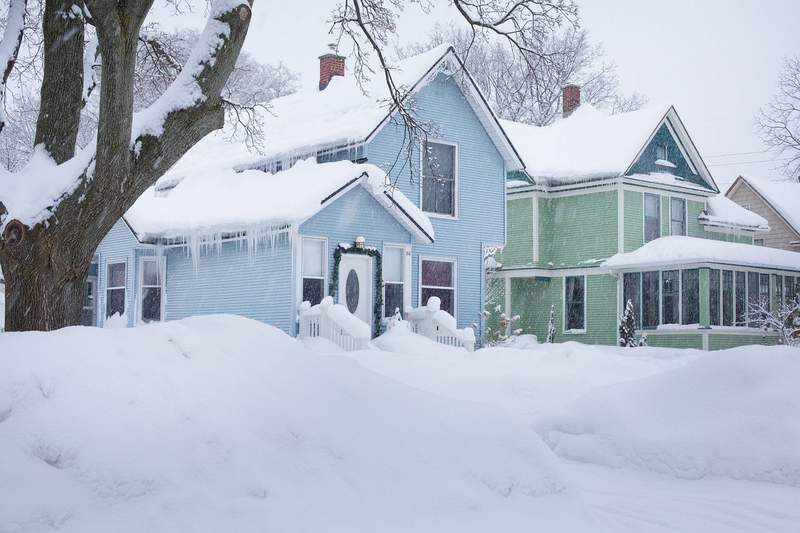 Snow falling on houses in a neighborhood.