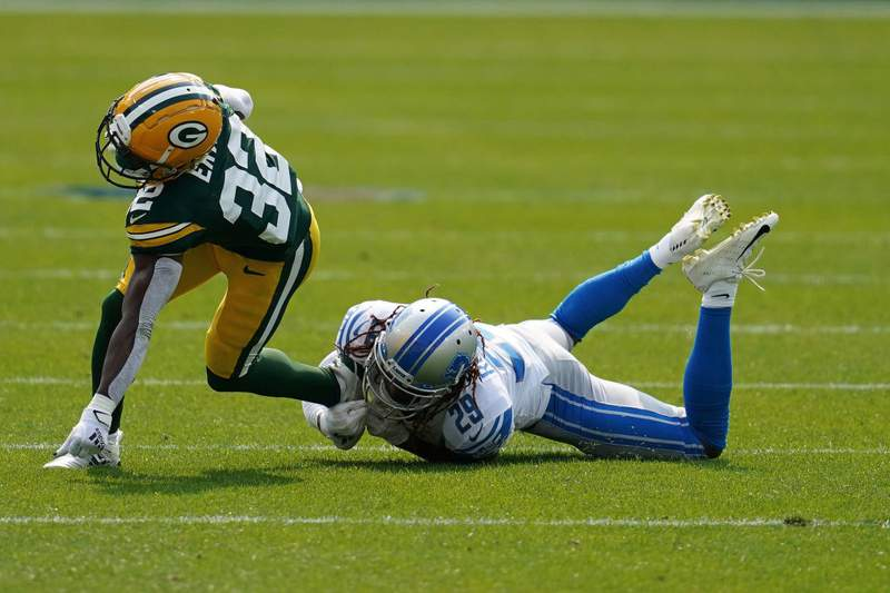 GREEN BAY, WISCONSIN - SEPTEMBER 20:  Tyler Ervin #32 of the Green Bay Packers is tripped up by Darryl Roberts #29 of the Detroit Lions during the second quarter at Lambeau Field on September 20, 2020 in Green Bay, Wisconsin. (Photo by Stacy Revere/Getty Images)