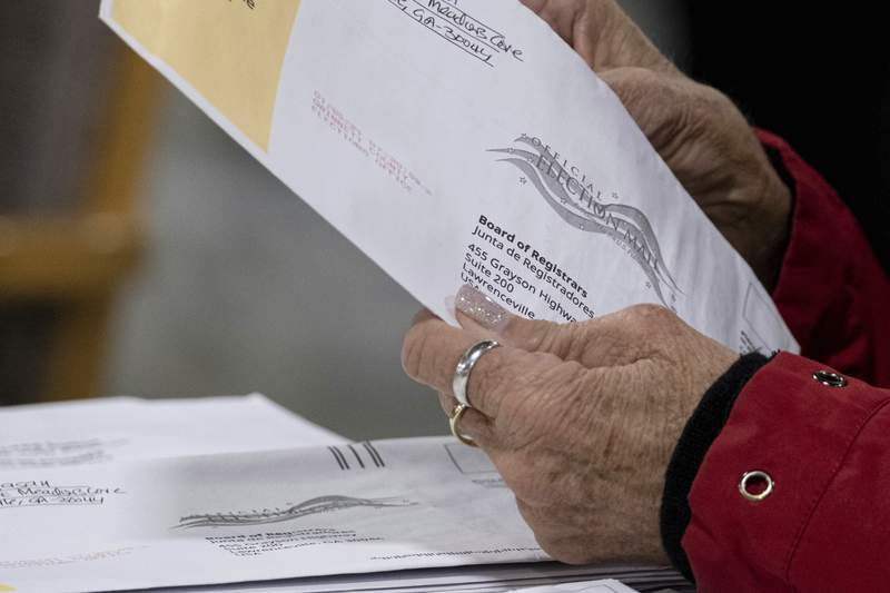 Workers at the Gwinnett County Georgia elections headquarters process absentee ballots for Georgia's Senate runoff election in Lawrenceville, Ga. on Wednesday,  Jan. 6, 2021. (AP Photo/Ben Gray)
