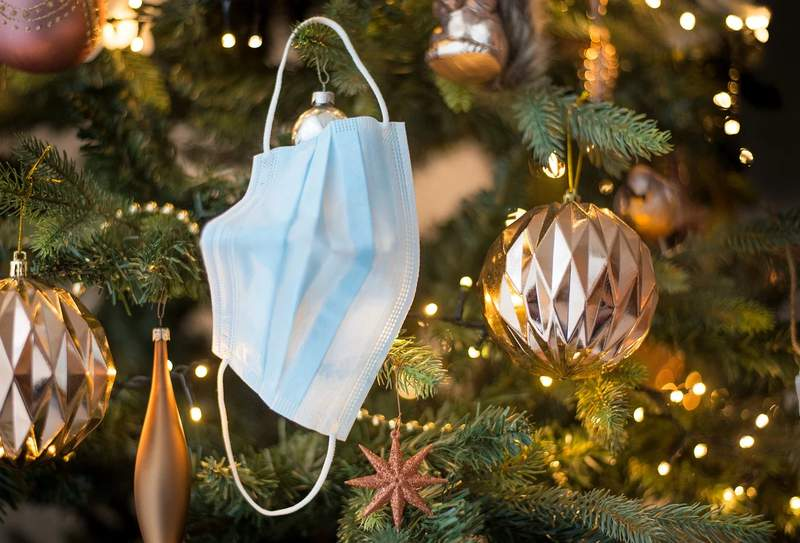 A face mask hangs on a Christmas tree.