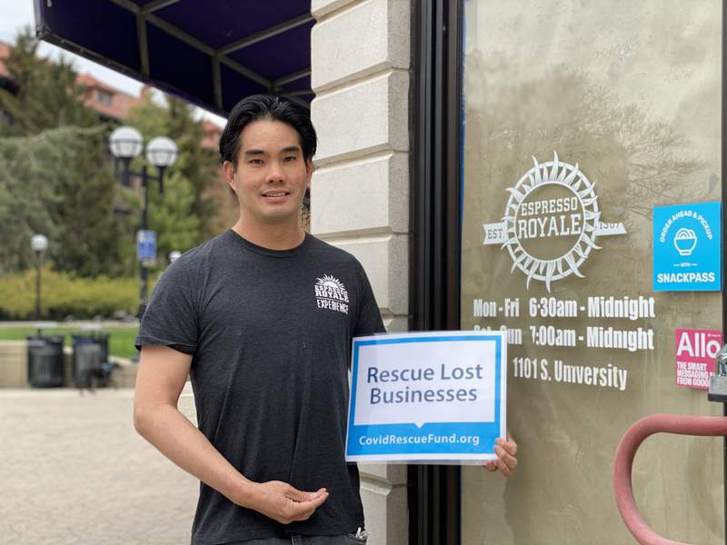 David Lin poses with a sign promoting the COVID Rescue Fund outside his shuttered Espresso Royale coffee shop on 1101 S University Ave. on April 26, 2021.