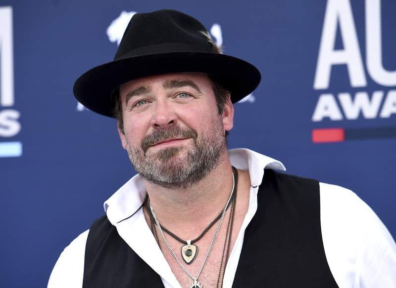 FILE - In this Sunday, April 7, 2019 file photo, Lee Brice arrives at the 54th annual Academy of Country Music Awards at the MGM Grand Garden Arena  in Las Vegas. Country singer Lee Brice tested positive for COVID-19 and will not perform as scheduled at the CMA Awards on Wednesday, Nov. 11, 2020.  (Photo by Jordan Strauss/Invision/AP)