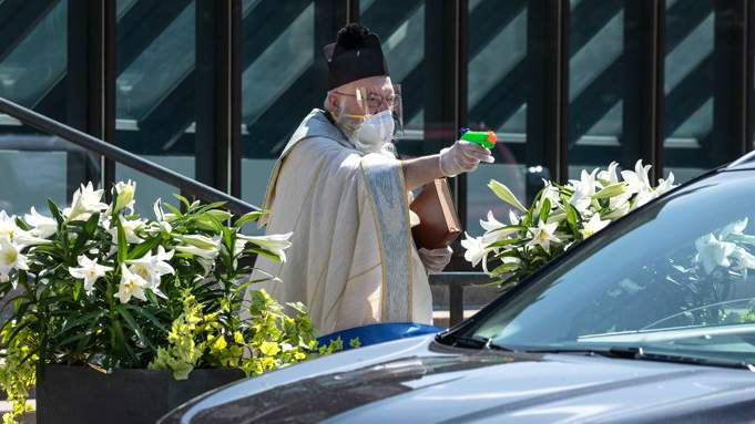 Father Tim Pelc of Detroit's St. Ambrose Perish uses a water gun to bless churchgoers with holy water during Holy Week in April 2020.