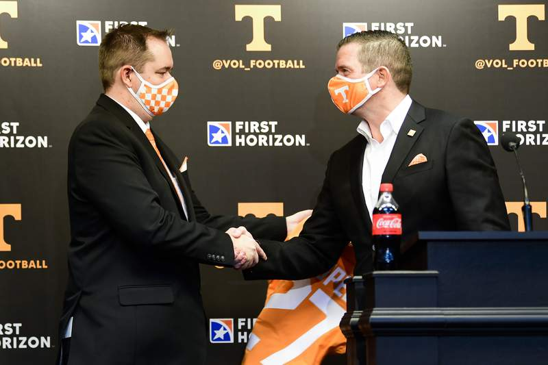 New Tennessee NCAA college football head coach Josh Heupel, left, shakes hands with University of Tennessee athletics director Danny White after being presented a jersey speaks during an introductory press conference at Neyland Stadium in Knoxville, Tenn., Wednesday, Jan. 27, 2021. (Caitie McLekin/Knoxville News Sentinel via AP, Pool)