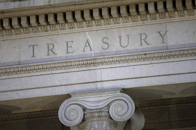 FILE- This June 6, 2019, file photo shows the U.S. Treasury Department building at dusk in Washington.  The U.S. Treasury has removed Vietnam and Switzerland from the list of nations labeled as currency manipulators, reversing a decision made by the Trump administration in December. In it's semi-annual report to Congress on currency manipulation, the first under the Biden administration, the U.S. Treasury Department said Friday, April 16, 2021,  that no country currently meets the U.S. criteria. It said, however, that Vietnam, Switzerland, as well as Taiwan, will be placed under enhanced monitoring for their recent actions. (AP Photo/Patrick Semansky, File)